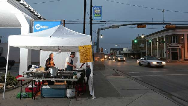 "Martin Herrera, 49, in apron, sets up his taco tent in Kenedy at 4 a.m. most weekdays. ""I follow the money,"" says the San Antonio entrepreneur, who'll sell up to 500 tacos to oil field workers. Photo: Jerry Lara / ©2013 San Antonio Express-News"