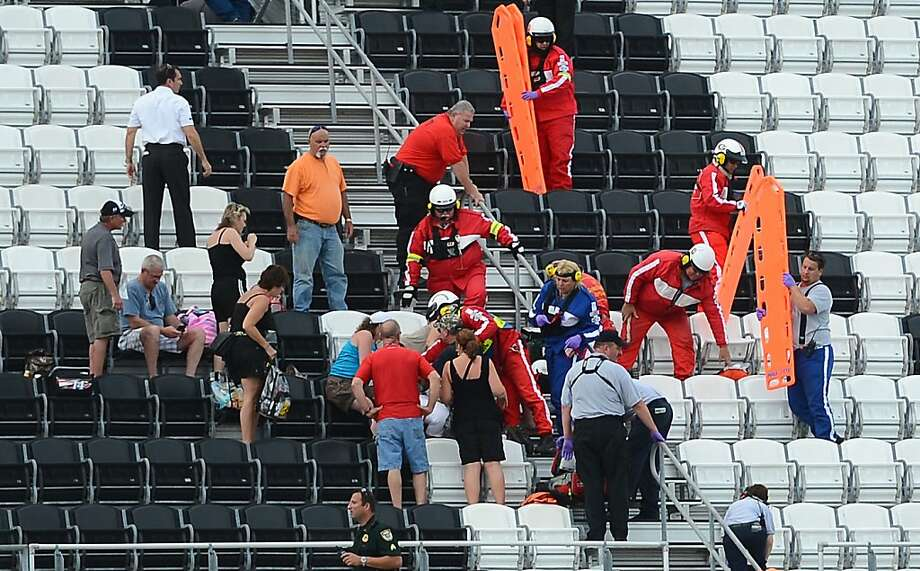 Emergency help injured spectators in the upper level of the front grandstand at Daytona International Speedway after a wreck on the final lap of the DRIVE4COPD 300 at Daytona International Speedway in Daytona Beach, Florida, Saturday, February 23, 2013  During the wreck, Kyle Larson's Chevrolet got lofted into the catch fence and the front end and engine along with other debris of Larson's car tore into the fence. (Jeff Siner/Charlotte Observer/MCT) Photo: Jeff Siner, McClatchy-Tribune News Service