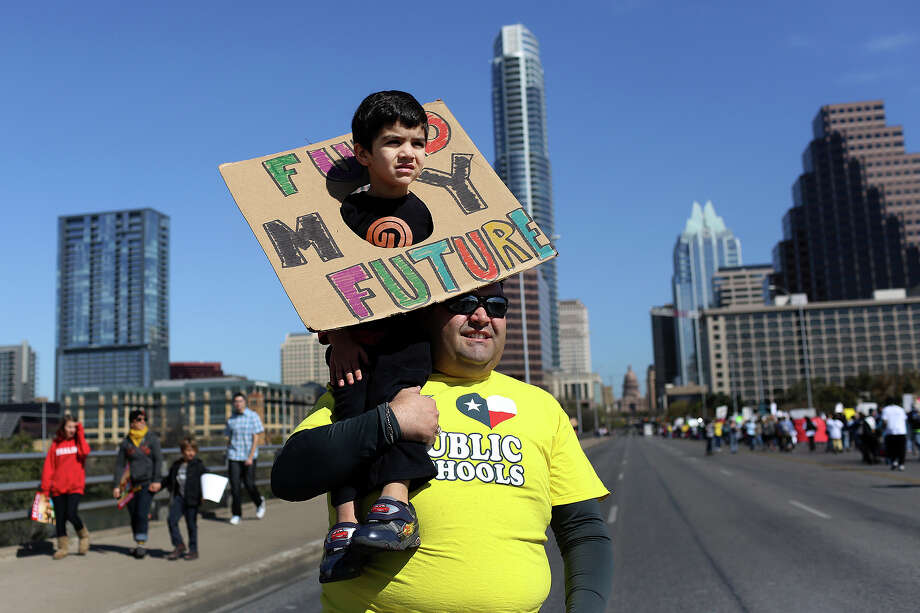 Noel Candelaria, Vice President of the Texas State Teacher Association, carries his son, Patrick, 3, as they join the the Save Texas Schools March on the Congress Ave. bridge to the Texas State Capitol for a rally in Austin on Saturday, Feb. 23, 2013. Photo: Lisa Krantz, San Antonio Express-News / San Antonio Express-News