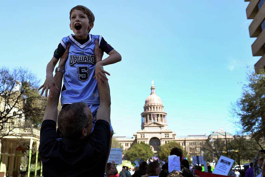 Lincoln Kilday, 7, gasps as his father, Doug Kilday, of Austin, holds him up so he can see the hundreds of marchers behind them during the Save Texas Schools March to the Texas State Capitol for a rally in Austin on Saturday, Feb. 23, 2013. Photo: Lisa Krantz, San Antonio Express-News / San Antonio Express-News