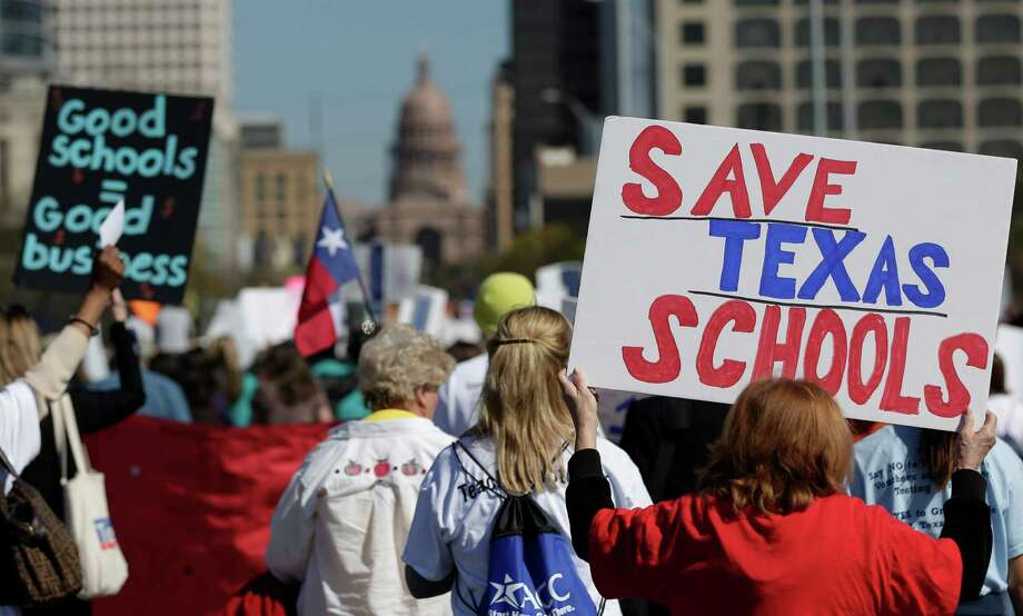 Teachers, students, parents and school administrators march up Congress Avenue as they take part in a rally for Texas public schools at the state Capitol, Saturday, Feb. 23, 2013, in Austin, Texas. About 2,000 teachers, students, parents and school administrators rallied at the state Capitol, demanding that the Legislature reverse $5.4 billion in cuts to public education amid new data that Texas now spends less per-pupil than almost anywhere else in America. (AP Photo/Eric Gay) Photo: Eric Gay, Associated Press / AP