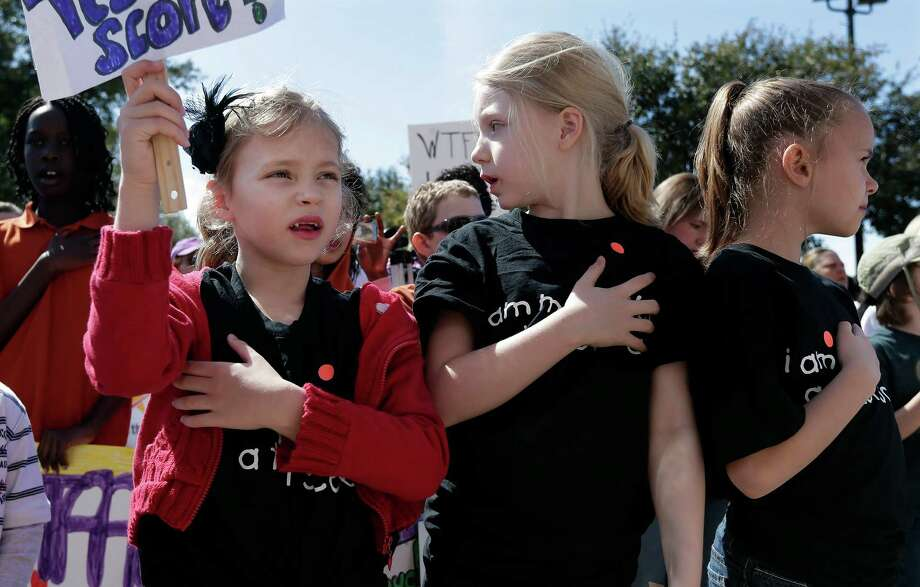 Frisco, Texas students, Cate Foughty, 6, left, Emma Foughty, 8, center, and Sophie Gray, 8, right, hold a hand over their heart during the national anthem as they take part in a rally for Texas public schools at the state Capitol, Saturday, Feb. 23, 2013, in Austin, Texas. About 2,000 teachers, students, parents and school administrators rallied at the state Capitol, demanding that the Legislature reverse $5.4 billion in cuts to public education amid new data that Texas now spends less per-pupil than almost anywhere else in America.(AP Photo/Eric Gay) Photo: Eric Gay, Associated Press / AP