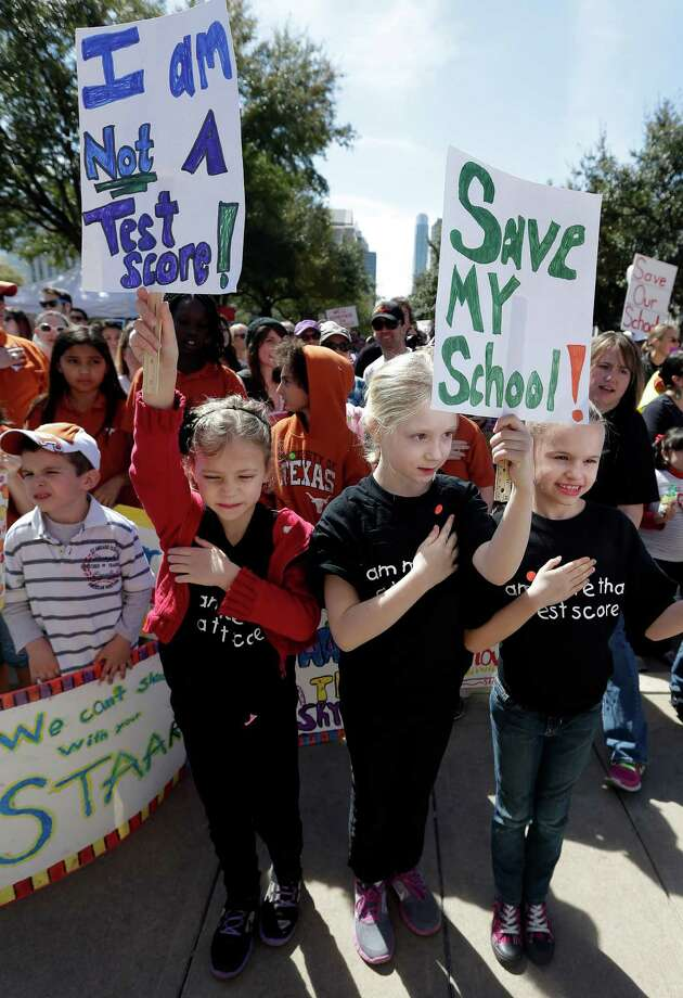 Frisco, Texas, students, Cate Foughty, 6, left, Emma Foughty, 8, center, and Sophie Gray, 8, right, hold a hand over their heart during the national anthem as they take part in a rally for Texas public schools at the state Capitol, Saturday, Feb. 23, 2013, in Austin, Texas. About 2,000 teachers, students, parents and school administrators rallied at the state Capitol, demanding that the Legislature reverse $5.4 billion in cuts to public education amid new data that Texas now spends less per-pupil than almost anywhere else in America. (AP Photo/Eric Gay) Photo: Eric Gay, Associated Press / AP