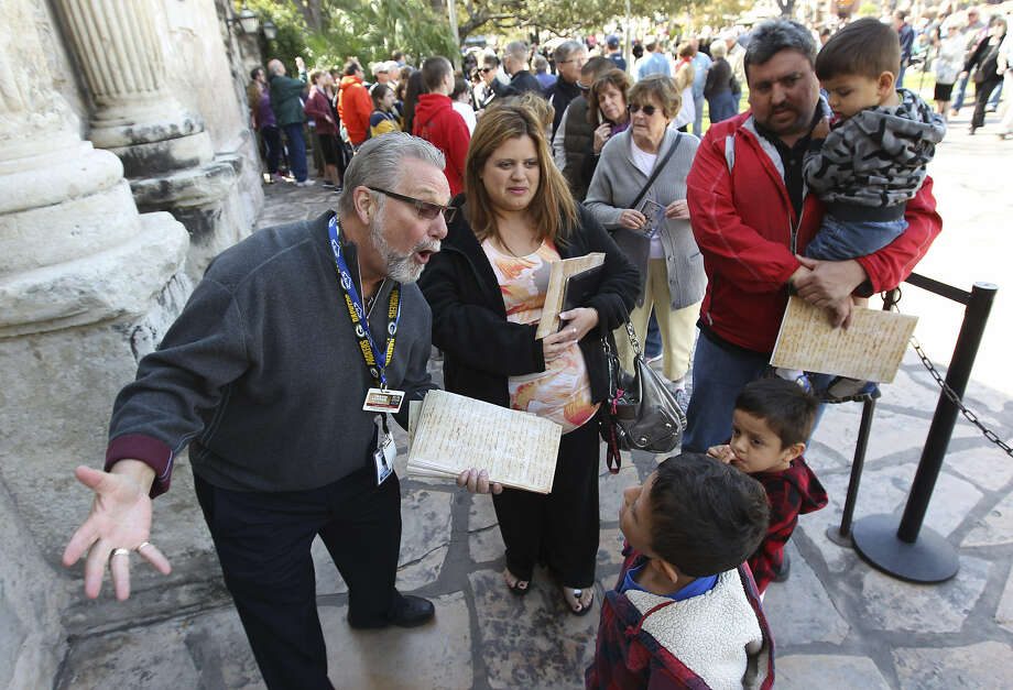 "Volunteer docent Don Townsend (left) talks to the children of Vanessa and Jose Soto while the family waits to get in to see the ""victory or death"" letter."
