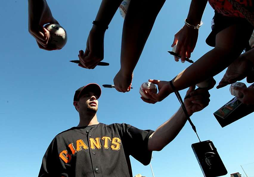 In Scottsdale, Ariz., first baseman Brandon Belt signs autographs for fans before the Giants' first