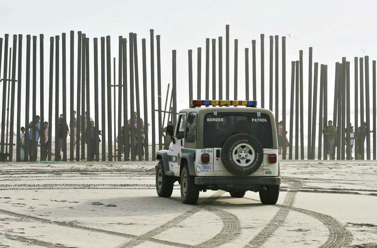 A U.S. Border Patrol vehicle sits parked in front of a crowd of people peering through the U.S.-Mexico border fence in San Diego, Calif., once a more popular illegal entry area.