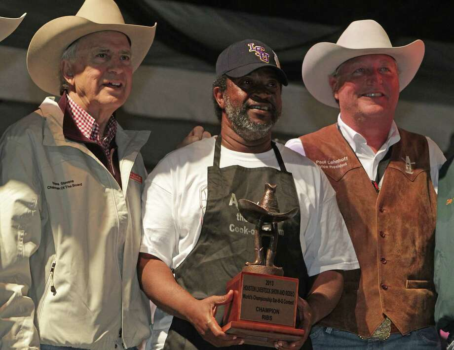 "Kerry Fellows, center, accepts the Champion Ribs trophy for team ""Across the Track Cook-off Team"" with Houston Livestock Show and Rodeo Chairman Steve Stevens left, and Vice-President Paul Lehnhoff right, at the Houston Livestock Show and Rodeo World's Championship Bar-B-Que Contest in Reliant Park Saturday, Feb. 23, 2013, in Houston. ""Across the Track Cook-off Team"" also won Overall Grand Champion. Photo: James Nielsen, Houston Chronicle / © 2013  Houston Chronicle"