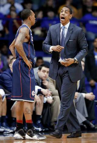 Connecticut coach Kevin Ollie, right, talks with Ryan Boatright during the first half of an NCAA college basketball game against DePaul in Rosemont, Ill., on Saturday, Feb. 23, 2013. (AP Photo/Nam Y. Huh) Photo: Nam Y. Huh, Associated Press / AP