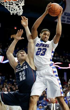 DePaul forward Donnavan Kirk, right, gets a rebound against Connecticut forward Leon Tolksdorf during the first half of an NCAA college basketball game in Rosemont, Ill., on Saturday, Feb. 23, 2013. (AP Photo/Nam Y. Huh) Photo: Nam Y. Huh, Associated Press / AP