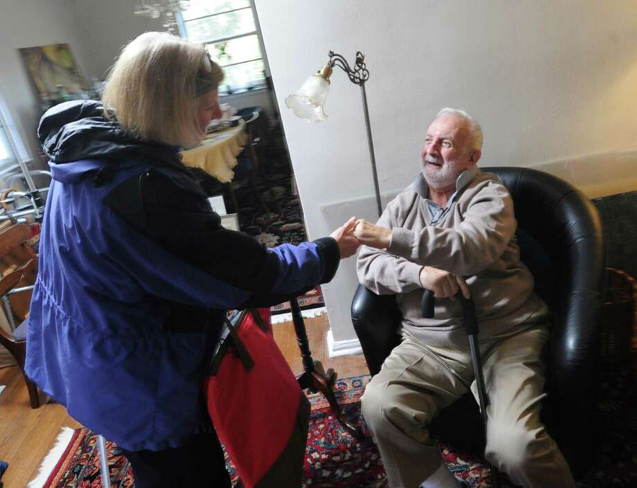 Gilbert Heller, seated, is greeted by Emily Cox, a care giver provided through At Home in Greenwich, in Heller's Greenwich home, Friday afternoon, Feb. 15, 2013. Gilbert has Parkinson's disease and both he and his wife receive assistance from Cox with basic tasks such as food shopping and help around their home. At Home Greenwich is a nonprofit, nonsectarian organization founded to help senior residents of Greenwich get access to life services and to a network of social connections and events. Photo: Bob Luckey / Greenwich Time
