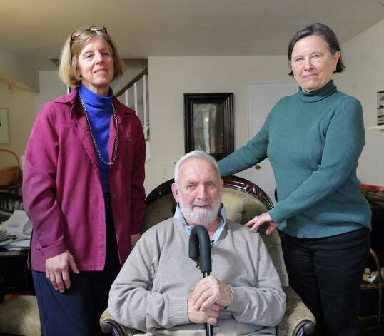 Gilbert Heller, seated, with his wife, Zdena, right, and Emily Cox, a care giver provided through At Home in Greenwich, in the Hellers' Greenwich home, Friday afternoon, Feb. 15, 2013. Gilbert suffers from Parkinson's disease and both he and his wife receive assistance from Cox with basic tasks such as food shopping and help around their home. At Home Greenwich is a nonprofit, nonsectarian organization founded to help senior residents of Greenwich get access to life services and to a network of social connections and events. Photo: Bob Luckey / Greenwich Time
