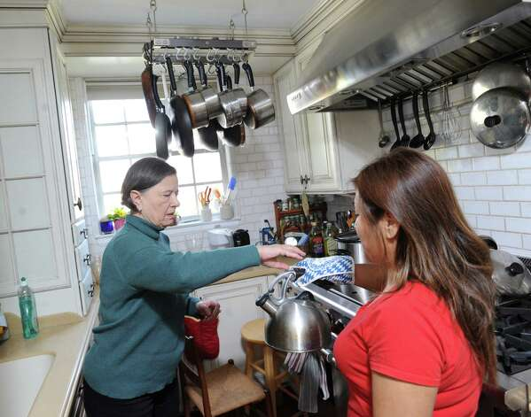 At left, Zdena Heller, gets help in the kitchen from Gladys Castaneda, a home-care helper, provided through At Home in Greenwich, in Heller's Greenwich home, Friday afternoon, Feb. 15, 2013. Zdena's husband, Gilbert, has Parkinson's disease and both he and his wife receive assistance from helpers provided through At Home Greenwich, a nonprofit, nonsectarian organization founded to help senior residents of Greenwich get access-to- life services and to a network of social connections and events. Photo: Bob Luckey / Greenwich Time