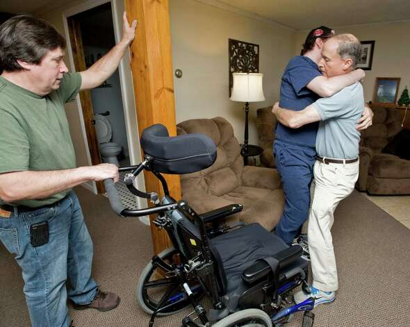 Gary Sand positions the wheelchair for his son, Gary, as he's helped to it by Guy La Grotta of Danbury, a certified nurses assistant, at Gary's home in Danbury. Gary, 33, was in a rollover car accident 11 years ago that caused significant brain stem injury. Saturday, Feb. 2 Photo: Scott Mullin / The News-Times Freelance