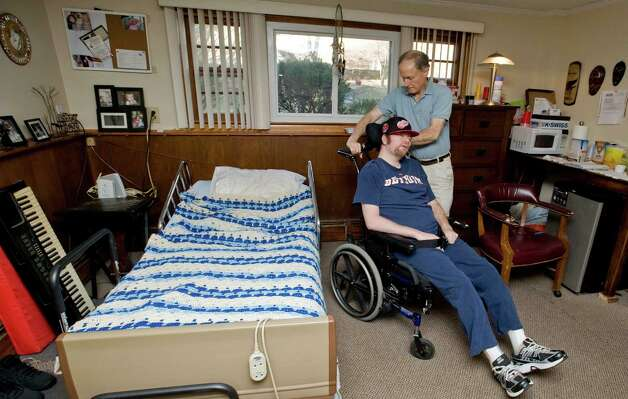 Gary Sand, 33, was in a rollover car accident 11 years ago that caused significant brain stem injury. Caregiver Guy La Grotta of Danbury, a certified nurses assistant, positions the wheelchair next to the bed at Gary's home in Danbury. Saturday, Feb. 2 Photo: Scott Mullin