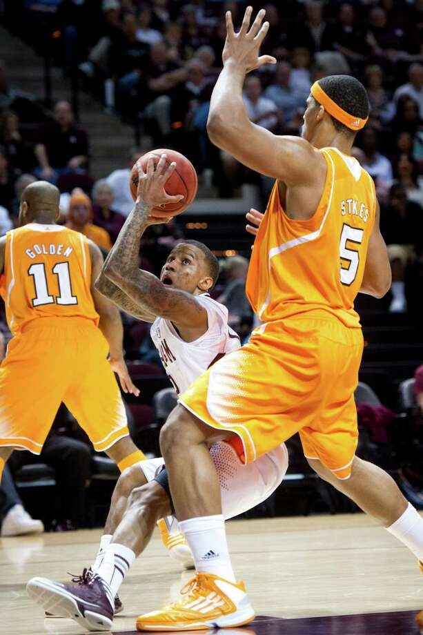 Tennessee's Jarnell Stokes (5) looms large as Texas A&M's Fabyon Harris, center, goes up for a shot. Photo: Stuart Villanueva, MBR / Bryan College Station Eagle