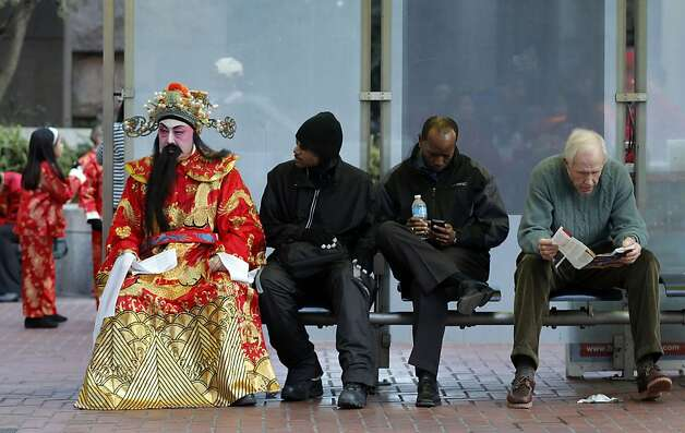 Rocky Lam, who said he was dressed as Cai Shen, the God of Fortune, takes a break as he waits for the Chinese New Year Parade to begin in San Francisco. Photo: Michael Macor, The Chronicle