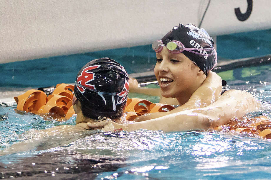 Johnson's Raquel Grays (right) and Churchill's Megan Strickland celebrate after the girls 50 yard freestyle in the finals of the 5A UIL Swimming & Diving State Meet at the Jamail Texas Swim Center in Austin on Saturday, Feb 23, 2013.  Grays took gold in the event with a time of 23.37 while Strickland took bronze with a time of 23.51.  MARVIN PFEIFFER/ mpfeiffer@express-news.net Photo: MARVIN PFEIFFER, Express-News / Express-News 2013