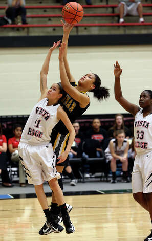 Kiara Etheridge goes up over Jacquelyn Adkins to score for the Bears as Brennan plays Vista Ridge in the girls Region  IV-4A championship basketball game at Littleton Gym on February 23, 2013. Photo: TOM REEL, Express-News