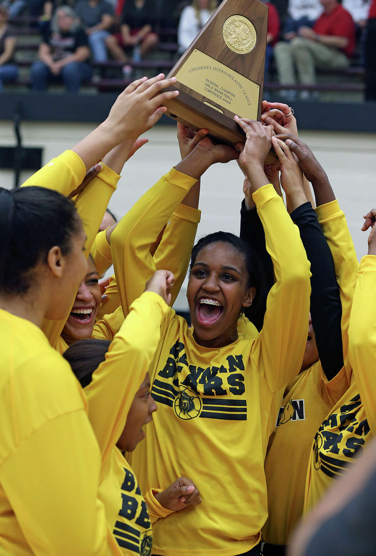 Tanaeya Boclair hoists the trophy after Brennan beats Vista Ridge in the girls Region IV-4A championship basketball game at Littleton Gym on February 23, 2013.