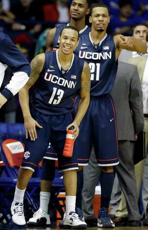 Connecticut guard Shabazz Napier (13) and guard Omar Calhoun (21) smile as they cheer for teammates during the second half of an NCAA college basketball game against DePaul in Rosemont, Ill., on Saturday, Feb. 23, 2013. Connecticut won 81-69. (AP Photo/Nam Y. Huh) Photo: Nam Y. Huh, Associated Press / AP