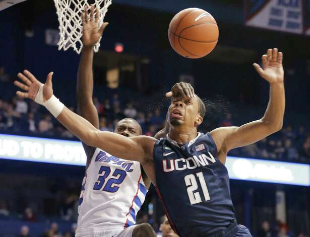 DePaul guard Charles McKinney (32) vies for a rebound with Connecticut guard Omar Calhoun (21) during the second half of an NCAA college basketball game in Rosemont, Ill., on Saturday, Feb. 23, 2013. Connecticut won 81-69. (AP Photo/Nam Y. Huh) Photo: Nam Y. Huh, Associated Press / AP
