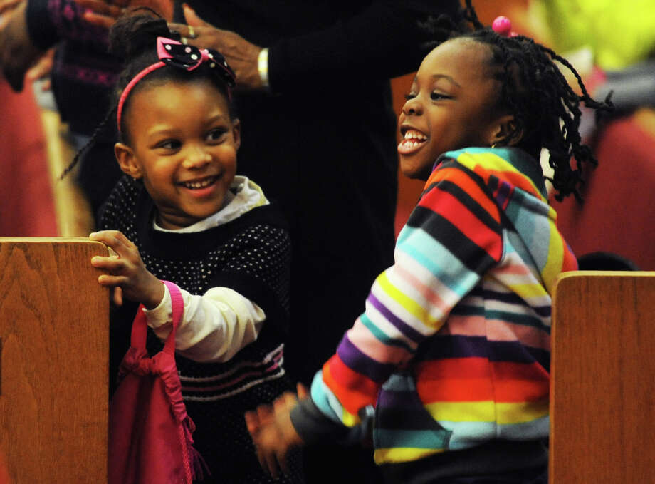 "Jahnia Brown, left, 4, and Anaiah William, 4, both of Danbury, Conn., dance to music sung by the New Hope Baptist Church youth mass choir at the Fourth Annual City-Wide Black History Month Program ""Youth Making a Difference in Black History"" at the New Hope Baptist Church in Danbury, Conn. Saturday, Feb. 23, 2013. The program featured prayer, music, dancing, acting and education about how young people helped make a difference in black history. Photo: Tyler Sizemore / The News-Times"