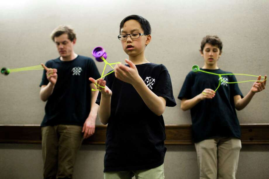 Yo-yo all stars Harrison Lee, 13, the 2012 international rookie of the year, center, Charles Haycock, 19, the 2011 Canadian champion, right, and Jensen Kimmitt, 24, the 2010 world champion, left, warm up in a quiet hallway before their performances at the ninth annual Pacific Northwest Regional Yo-Yo Contest on Saturday, Feb. 23, 2013, at the Seattle Center Armory. Photo: JORDAN STEAD / SEATTLEPI.COM
