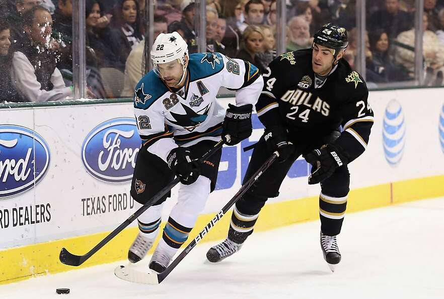 DALLAS, TX - FEBRUARY 23:  Dan Boyle #22 of the San Jose Sharks skates the puck against Eric Nystrom