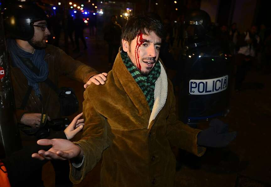 A protester bleeds after being injured during clashes at the end of a protest against government aus