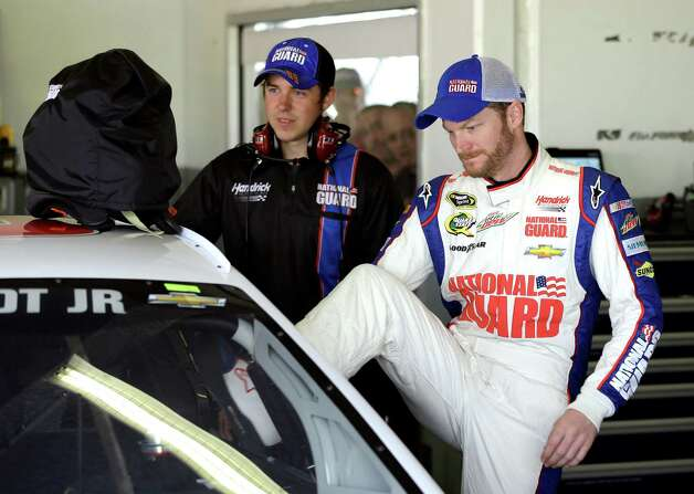 Dale Earnhardt Jr., right, climbs into his car during a practice session for the NASCAR Sprint Cup Series Daytona 500 auto race Friday, Feb. 22, 2013, at the Daytona International Speedway in Daytona Beach, Fla. (AP Photo/Chris O'Meara) Photo: Chris O'Meara