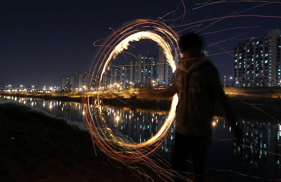 SEOUL, SOUTH KOREA - FEBRUARY 23:  A South Korean man spins a fire can during 'Jwibulnoli' a South Korean folk game at Han River on February 23, 2012 in Seoul, South Korea. The event is part of a 'Daeboreum', a Korean holiday that celebrates the first full moon of the lunar new year.  (Photo by Chung Sung-Jun/Getty Images) *** BESTPIX *** Photo: Chung Sung-Jun, Getty Images