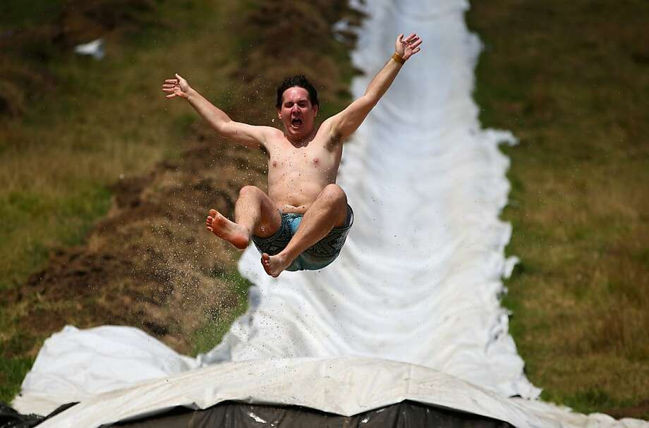 "AUCKLAND, NEW ZEALAND - FEBRUARY 23:  People enjoy the muddy thrills and spills on a waterslide dug into a hillside in Waimauku on February 23, 2013 in Auckland, New Zealand. Only 2000 people will have the honour of riding the water slides, with one measuring 650 meters long built by New Zealanders Jimi Hunt and Dan Drupstee, of the ""Live more Awesome"" charity this weekend. The world's longest slide will be open for only two days to  raise funds and awareness of depression.  (Photo by Phil Walter/Getty Images) *** BESTPIX *** Photo: Phil Walter, Getty Images"