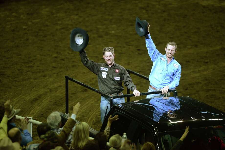 Drew Horner, left, and Buddy Hawkins acknowledge fans after winning the team roping competition at the San Antonio Stock Show & Rodeo on Saturday, Feb. 23, 2013. Photo: Billy Calzada, San Antonio Express-News / San Antonio Express-News