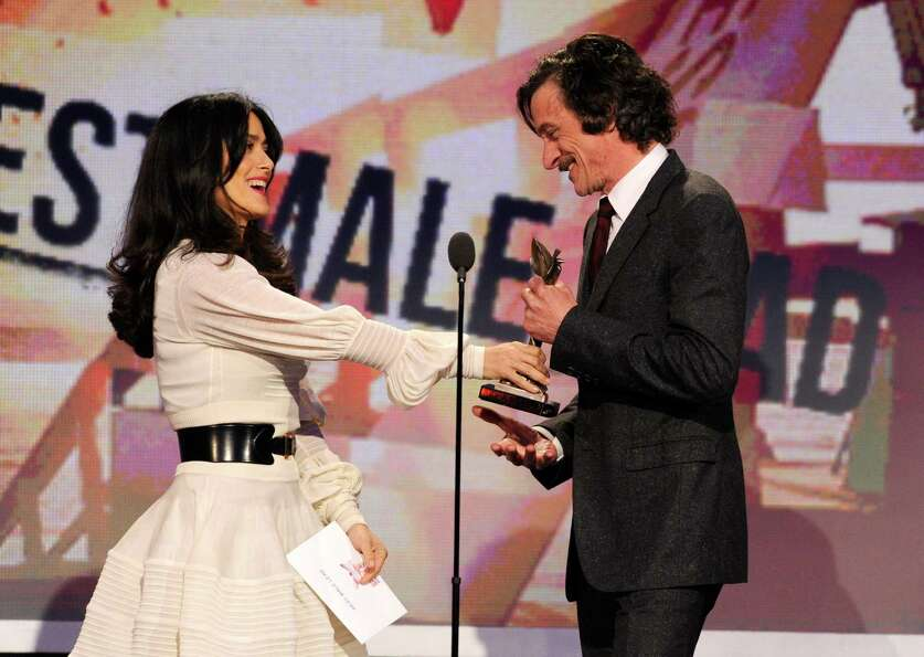 Actress Salma Hayek, left, presents John Hawkes with the award for best male lead for