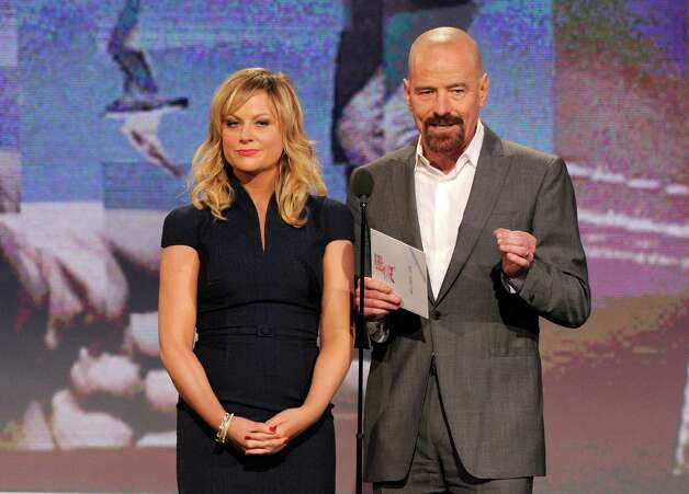 Amy Poehler, left, and Bryan Cranston speak onstage. Photo: Chris Pizzello/Invision/AP