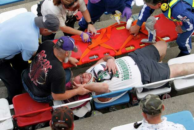 An injured spectator is treated after a crash at the conclusion of the NASCAR Nationwide Series auto race Saturday, Feb. 23, 2013, at Daytona International Speedway in Daytona Beach, Fla. Driver Kyle Larson's car hit the safety fence sending car parts and other debris flying into the stands.(AP Photo/David Graham) Photo: David Graham