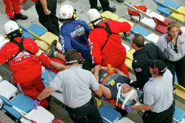 An injured spectators are treated after a crash at the conclusion of the NASCAR Nationwide Series auto race Saturday, Feb. 23, 2013, at Daytona International Speedway in Daytona Beach, Fla. Driver Kyle Larson's car hit the safety fence sending car parts and other debris flying into the stands. (AP Photo/David Graham) Photo: David Graham