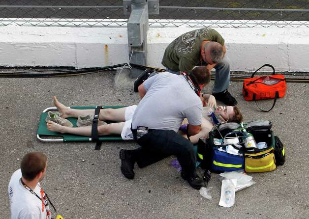 An injured spectator is treated after a crash at the conclusion of the NASCAR Nationwide Series auto race Saturday, Feb. 23, 2013, at Daytona International Speedway in Daytona Beach, Fla. Driver Kyle Larson's car hit the safety fence sending car parts and other debris flying into the stands. (AP Photo/David Graham) Photo: David Graham