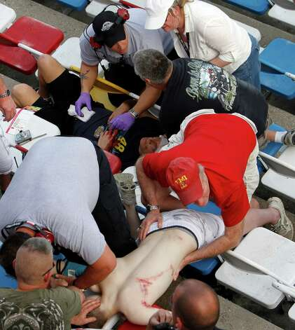 Injured spectators are treated after a crash at the conclusion of the NASCAR Nationwide Series auto race Saturday, Feb. 23, 2013, at Daytona International Speedway in Daytona Beach, Fla. Driver Kyle Larson's car hit the safety fence sending car parts and other debris flying into the stands. (AP Photo/David Graham) Photo: David Graham