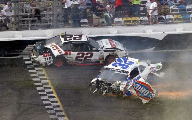 Brad Keselowski (22) and Kyle Larson (32) slide across the finish line after they were involved in a mulit-car crash on the final lap of the NASCAR Nationwide Series auto race at Daytona International Speedway, Saturday, Feb. 23, 2013, in Daytona Beach, Fla. (AP Photo/John Raoux) Photo: John Raoux