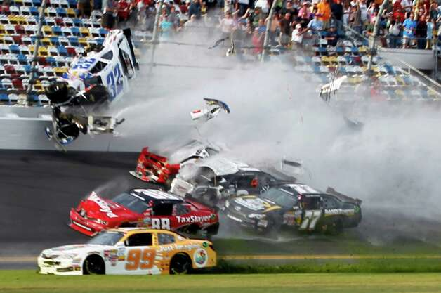 Kyle Larson (32) goes into the catch fence during a crash involving, among others, Justin Allgaier (31), Brian Scott (2), Parker Klingerman (77) and Dale Earnhardt Jr. (88) at the conclusion of the NASCAR Nationwide Series auto race Saturday, Feb. 23, 2013, at Daytona International Speedway in Daytona Beach, Fla. Getting past is Alex Bowman (99). (AP Photo/Terry Renna) Photo: Terry Renna