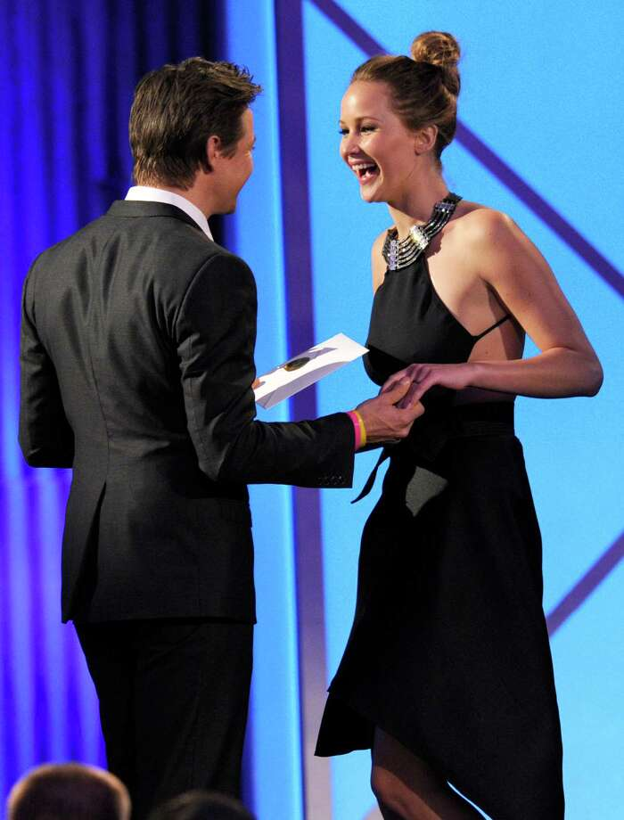 "Actor Jeremy Renner, left, presents actress Jennifer Lawrence with the award for best female lead for ""Silver Linings Playbook."" Photo: Chris Pizzello/Invision/AP"