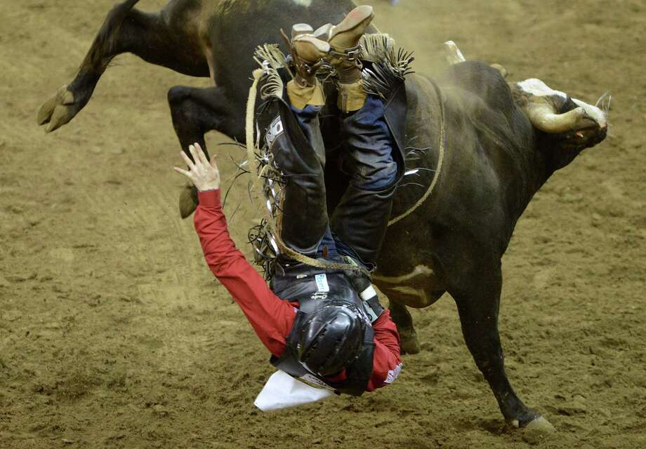Cody Teel is bucked off during the bull riding competition in the San Antonio Stock Show & Rodeo on Saturday, Feb. 23, 2013. Photo: Billy Calzada, San Antonio Express-News / San Antonio Express-News