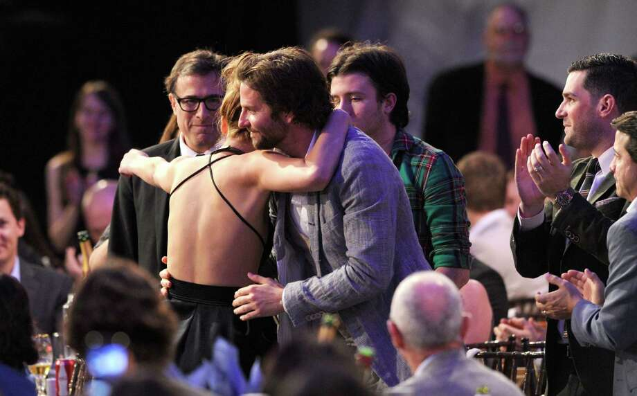 "Actress Jennifer Lawrence reacts after winning the award for best female lead for ""Silver Linings Playbook."" At left is director David O. Russell and co-star Bradley Cooper is at right. Photo: Chris Pizzello/Invision/AP"