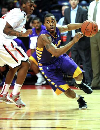 Albany's Mike Black drives the ball down the court as Fairfield's Justin Jenkins defends Saturday, F