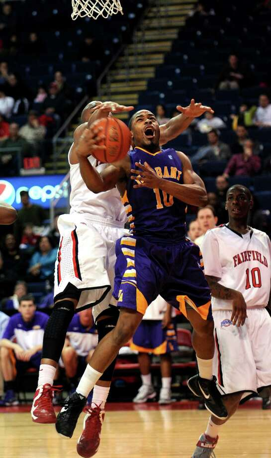 Albany's Mike Black gets fouled by Fairfield's Keith Matthews as he goes up for a shot during the second half of game action Saturday, Feb. 23, 2013 at the Webster Bank Arena in Bridgeport, Conn. Photo: Autumn Driscoll / Connecticut Post