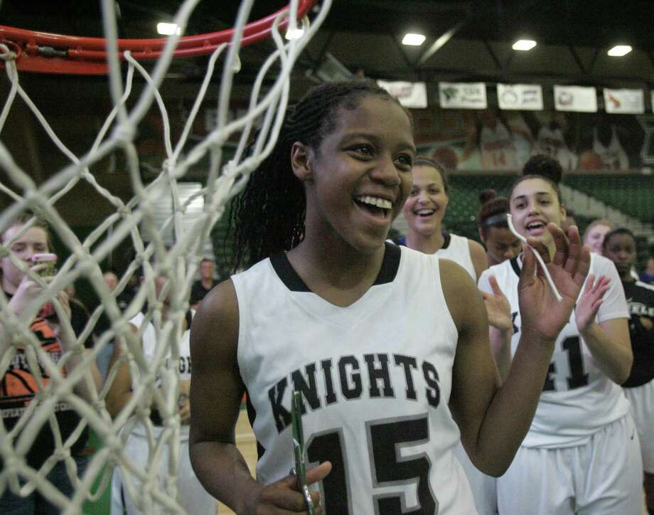 Steele's Kyra Lambert flashes a smile after cutting off a piece of the net during the Knights' victory celebration Saturday in Edinburg. Photo: Delcia Lopez / Special To The Express-News