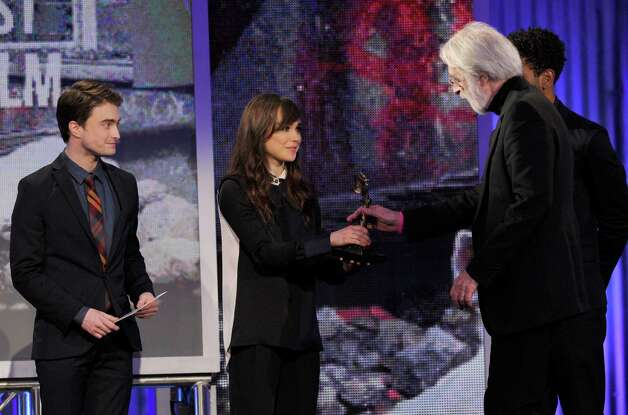 "Daniel Radcliffe, from left, and Ellen Page present Michael Haneke with the award for best international film for ""Amour."" Photo: Chris Pizzello/Invision/AP"