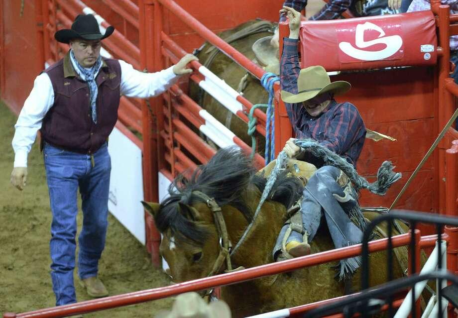 Saddle bronc rider Tyler Corrington exits the chute during the San Antonio Stock Show & Rodeo on Saturday, Feb. 23, 2013. Photo: Billy Calzada, San Antonio Express-News / San Antonio Express-News