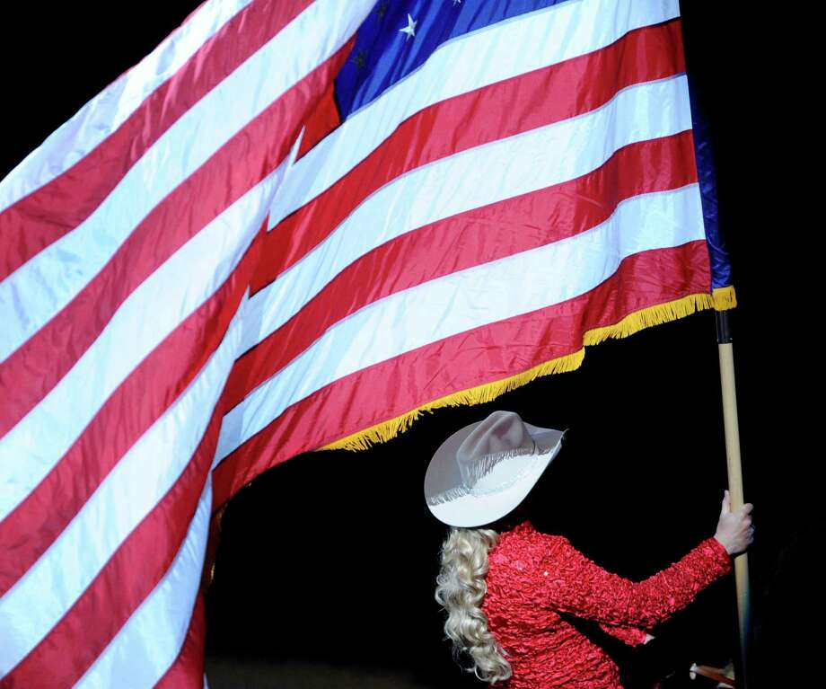 The Stars and Stripes is carried into the AT&T Center for the start of the San Antonio Stock Show & Rodeo on Saturday, Feb. 23, 2013. Photo: Billy Calzada, San Antonio Express-News / San Antonio Express-News